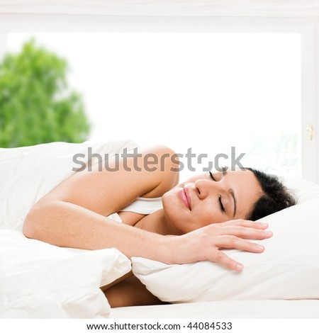Beautiful young woman sleeping on bed in her bedroom at home in the morning - stock photo