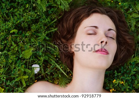 Beautiful young woman sleeping on grass. - stock photo
