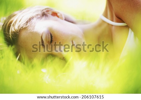 Beautiful young woman sleeping on grass outdoors - stock photo