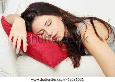 Beautiful young woman sleeping on sofa. - stock photo