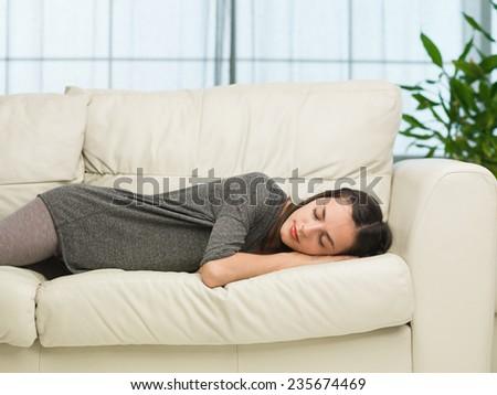 beautiful young woman sleeping on sofa at home - stock photo