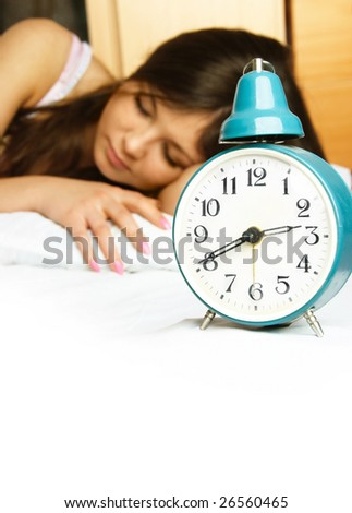 beautiful young woman sleeping peacefully in her bed with the alarm clock standing near her