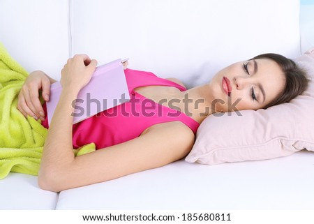 Beautiful young woman sleeping with book on sofa close up - stock photo