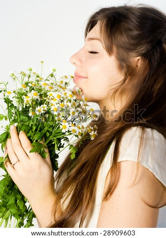 Beautiful young woman smell wildflowers - stock photo