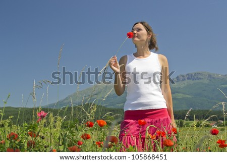 Beautiful young woman smelling a flower enjoying a perfect sunny day in the countryside