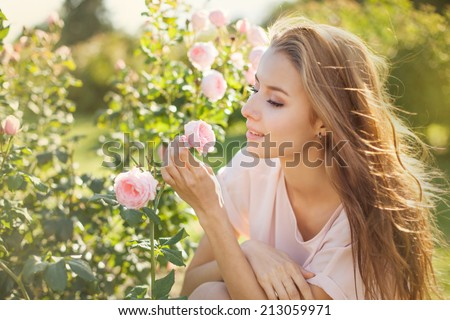 Beautiful young woman smelling a rose flower - stock photo