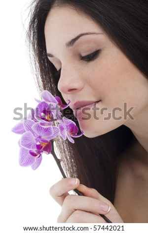 Beautiful young woman smelling flower - stock photo