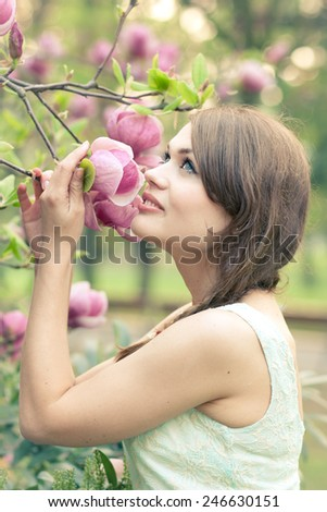 Beautiful young woman smelling freshly bloomed magnolias - stock photo