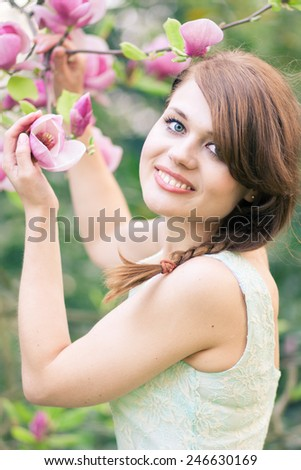 Beautiful young woman smelling freshly bloomed magnolias