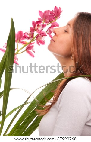 Beautiful young woman smelling natural purple orchid flower isolated on white background - stock photo