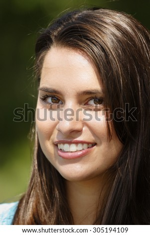 Beautiful young woman smiles at viewer. Focus is on near eye.
