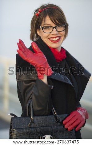 Beautiful young woman smiling and greeting on a sunny winter day. - stock photo