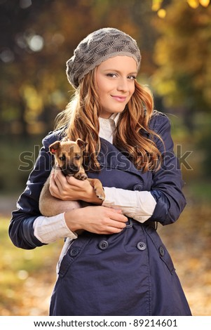 Beautiful young woman smiling and holding a puppy outdoors - stock photo