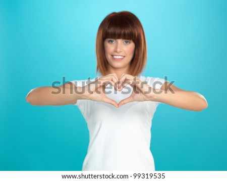 beautiful, young woman smiling and making a heart shape with her hands, on blue background