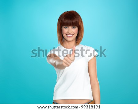 beautiful, young woman smiling and showing an ok sign with her hand, on blue background - stock photo