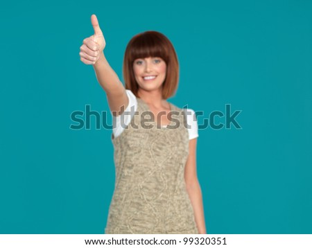 beautiful, young woman, smiling and showing her thumb up, on blue background - stock photo
