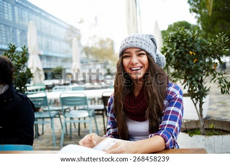 Beautiful young woman smiling brightly feeling so happy while sitting in sidewalk cafe, cute hipster girl choosing looking to you at beautiful coffee shop terrace, gorgeous female having fun - stock photo