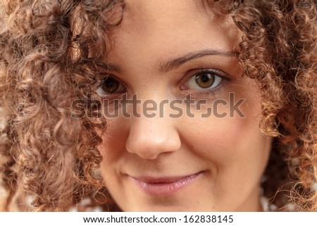Beautiful young woman smiling, gorgeous curly hair - stock photo