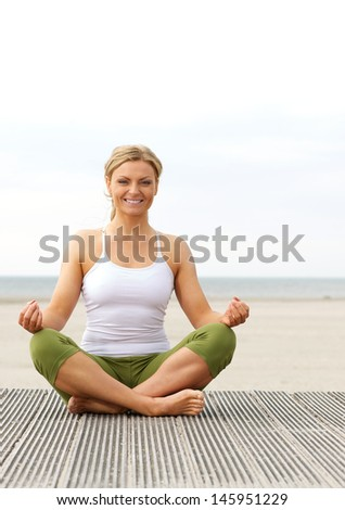 Beautiful young woman smiling in yoga pose outdoors