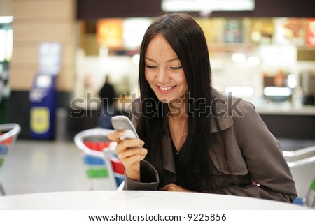 Beautiful young woman smiling looking at mobile phone. Shallow DOF. - stock photo