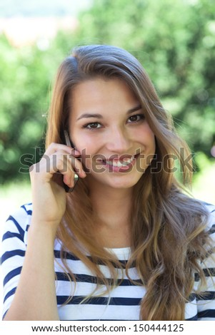Beautiful young woman smiling on the phone in a park  - stock photo