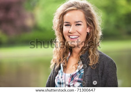 Beautiful young woman smiling outdoors - stock photo