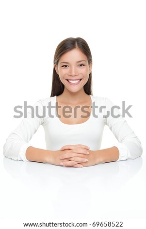 Beautiful young woman smiling sitting by table. Serene Asian Caucasian woman in white isolated on white background. - stock photo