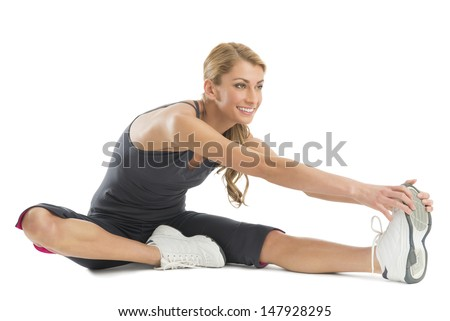Beautiful young woman smiling while stretching to touch her toes isolated against white background - stock photo