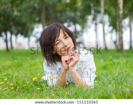 Beautiful young woman smiling with daisy in natural environment