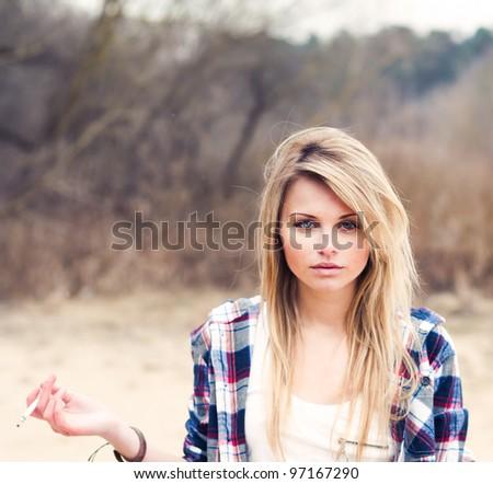 beautiful young woman smokes - stock photo