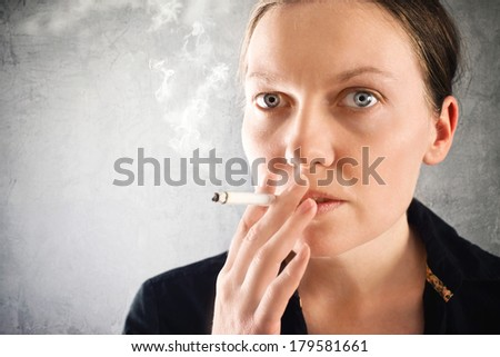 Beautiful young woman smoking cigarette, close up portrait.