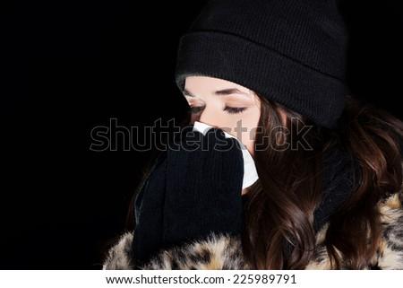 Beautiful young woman sneezing outside - stock photo