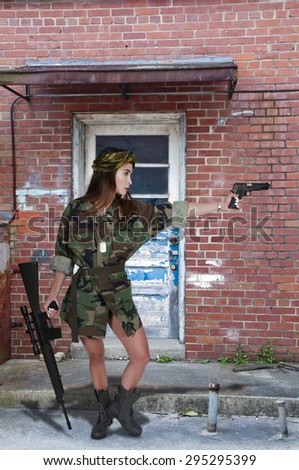 Beautiful young woman soldier with a pistol and rifle - stock photo