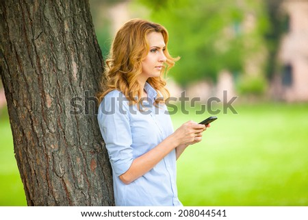 beautiful young woman speaking and texting on cellphone in a park with a happy mood