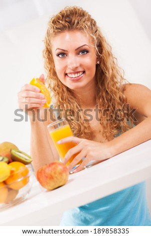 Beautiful young woman squeezes orange juice in the glass