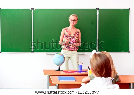 beautiful young woman standing at the blackboard and tells students a lesson - stock photo