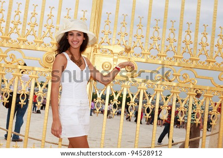Beautiful young woman standing by the golden gates of the Palace of Versailles in Paris, France. - stock photo