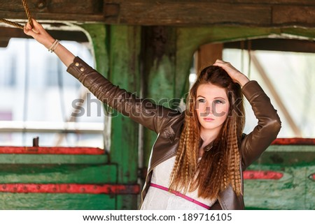 Beautiful young woman standing in a old wooden windmill - stock photo