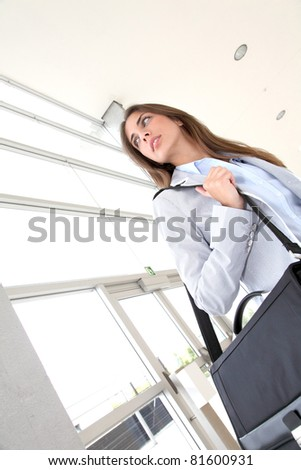 Beautiful young woman standing in hall with briefcase