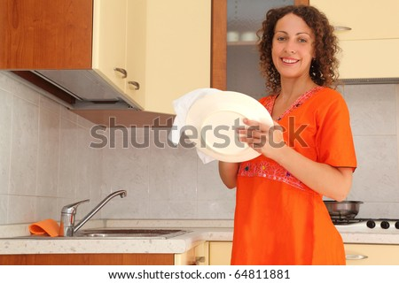 beautiful young woman standing in kitchen and wipes clean utensils - stock photo