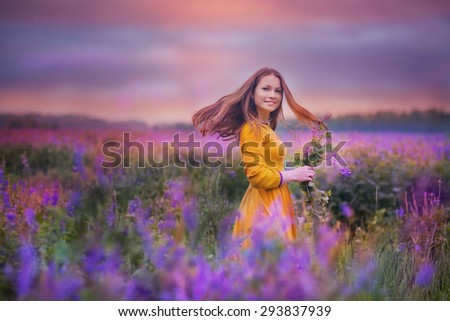 Beautiful young woman standing in the meadow of violet flowers at sunset - stock photo