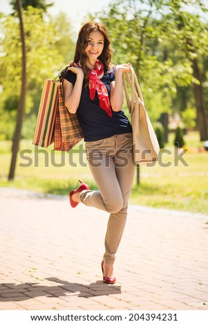 Beautiful young woman standing in the park and holding shopping bags.