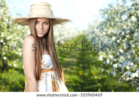 beautiful young woman standing near the apple tree on a warm summer day - stock photo