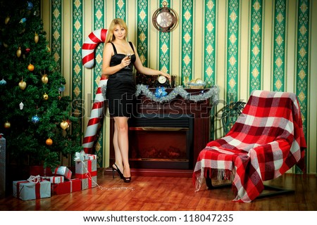 Beautiful young woman standing near the Christmas tree and fireplace at home. - stock photo