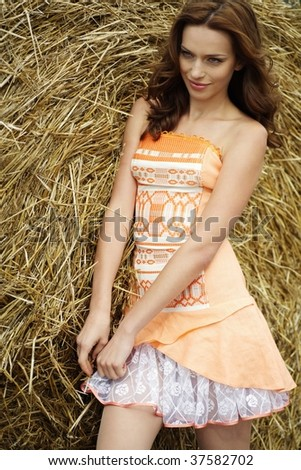 beautiful young woman standing near the round bale of hay on a field