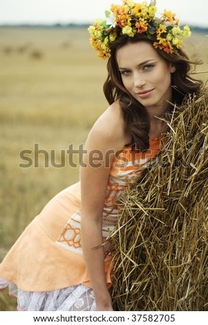 beautiful young woman standing near the round bale of hay on a field - stock photo