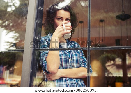beautiful young woman standing near window, drinking the coffee and looking into the distance