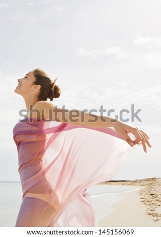 Beautiful young woman standing on a golden beach shore, with a pink fabric sarong around her body and floating with the breeze against a blue sky and sea during a summer vacation break. - stock photo
