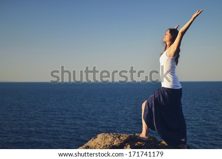 Beautiful young woman standing on a rock greeting the sea. - stock photo