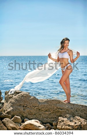 Beautiful young woman standing on a stone on the seashore